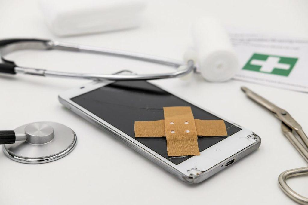 Kaputtes Smartphones mit verschiedenen Doktor-Utensilien wie Stethoskop und Pflaster